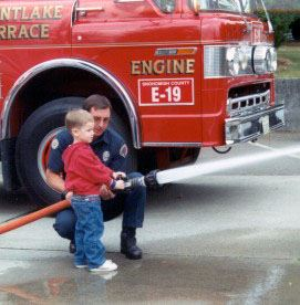 Fireman and little boy spray water by fire engine
